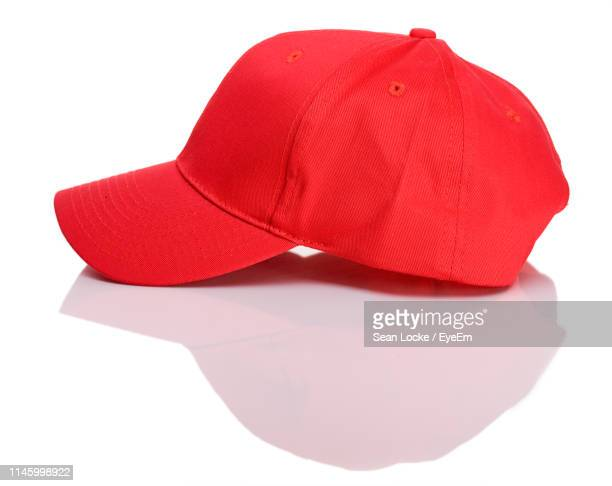 close-up of red cap against white background - baseball cap stock pictures, royalty-free photos & images