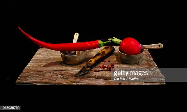 Close-Up Of Red Chili Pepper And Radish On Table Against Black Background