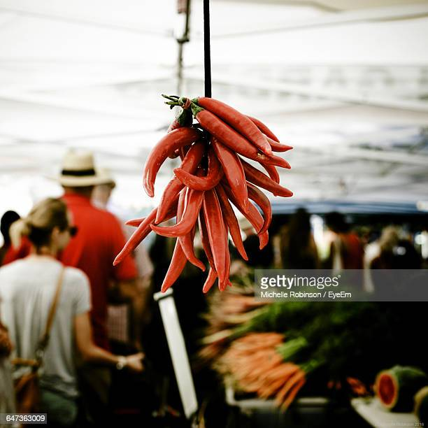 Close-Up Of Red Chili Pepper Hanging On Market Stall