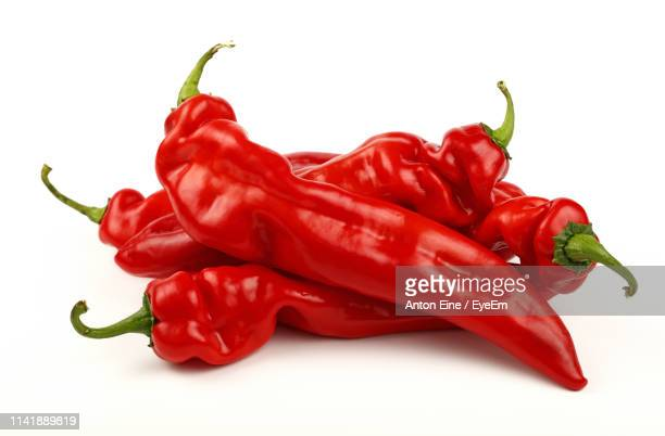 close-up of red chili peppers against white background - paprika stock pictures, royalty-free photos & images