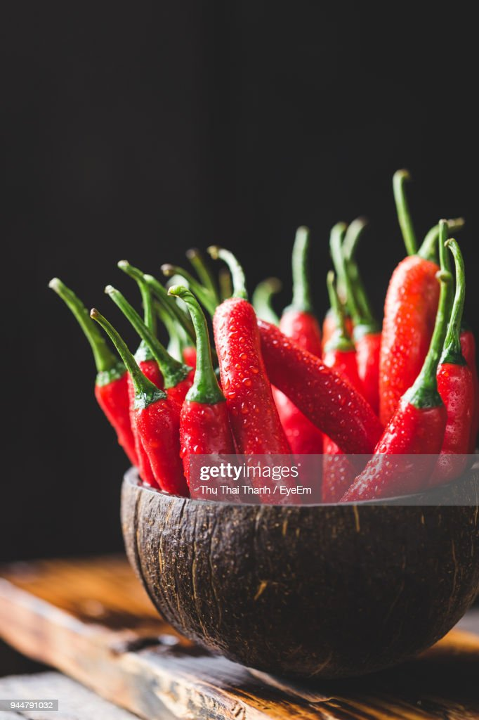 Close-Up Of Red Chili Peppers In Coconut Shell Against Black Background : Stock Photo