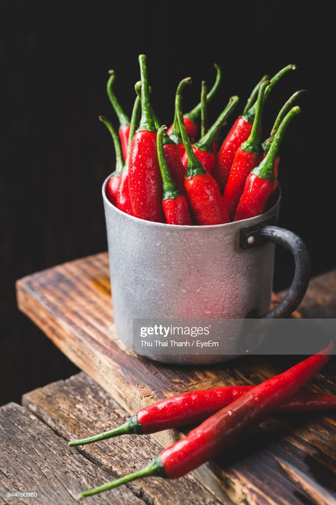 Close-Up Of Red Chili Peppers In Mug On Wood Against Black Background : Stock Photo