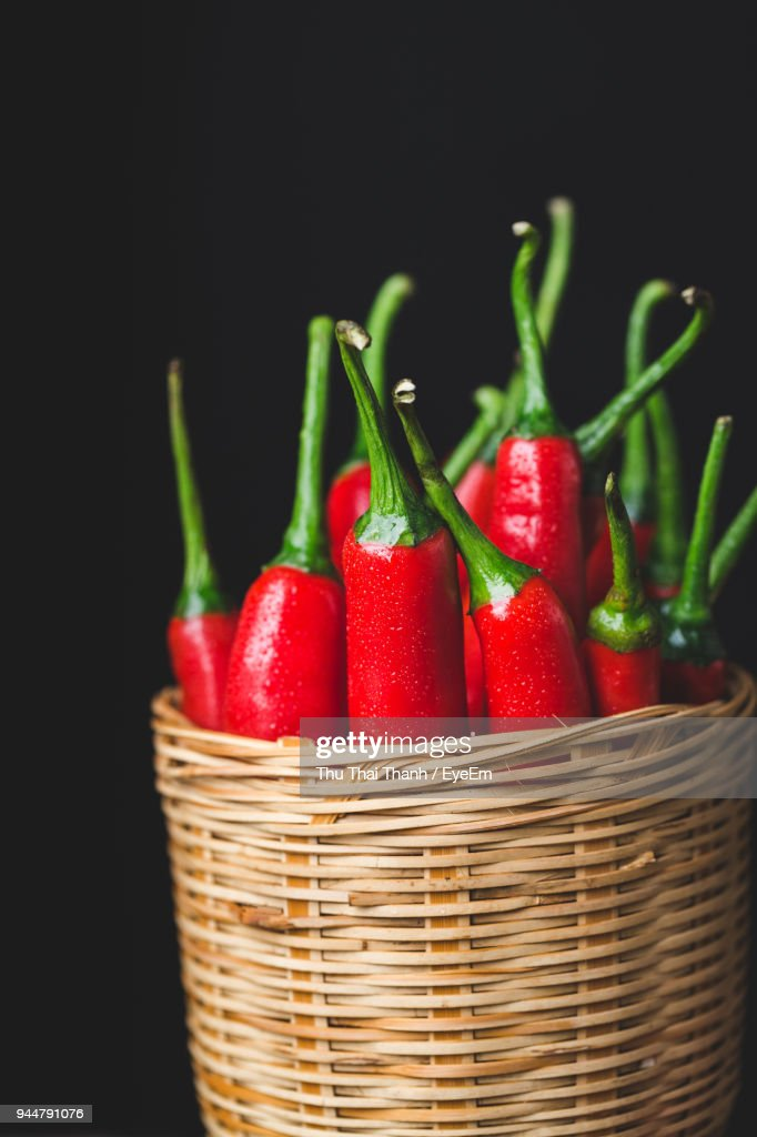 Close-Up Of Red Chili Peppers In Wicker Basket Against Black Background : Stock Photo