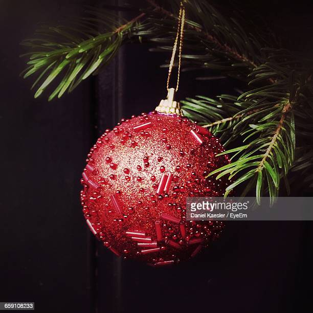 Close-Up Of Red Christmas Ball Hanging Against Black Background