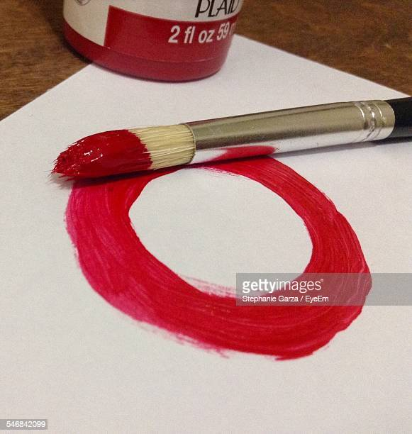 Close-Up Of Red Circle On Paper By Paintbrush