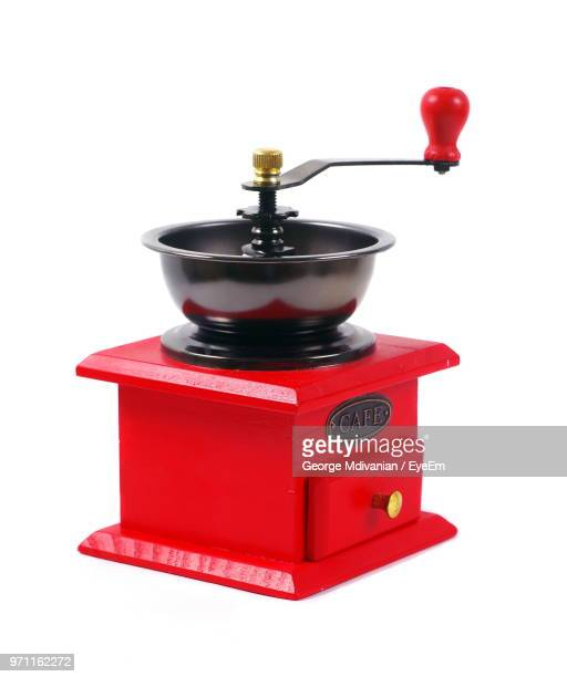 close-up of red coffee grinder against white background - coffee grinder stock photos and pictures