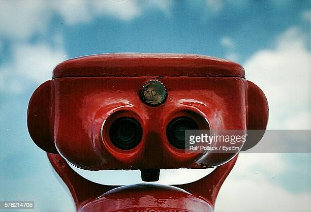 Close-Up Of Red Coin-Operated Binoculars Against Sky