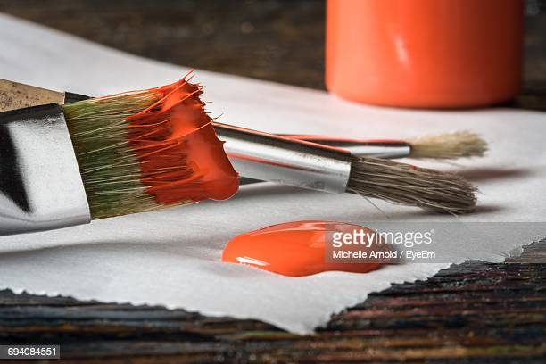 Close-Up Of Red Color And Brush On Table