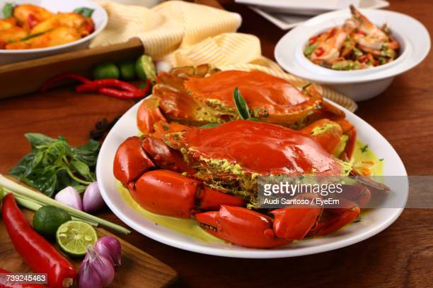 close-up of red crabs with sauce in plate by ingredients on table - chilli crab stock photos and pictures