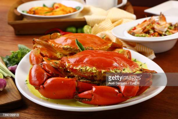 Close-Up Of Red Crabs With Sauce In Plate On Table