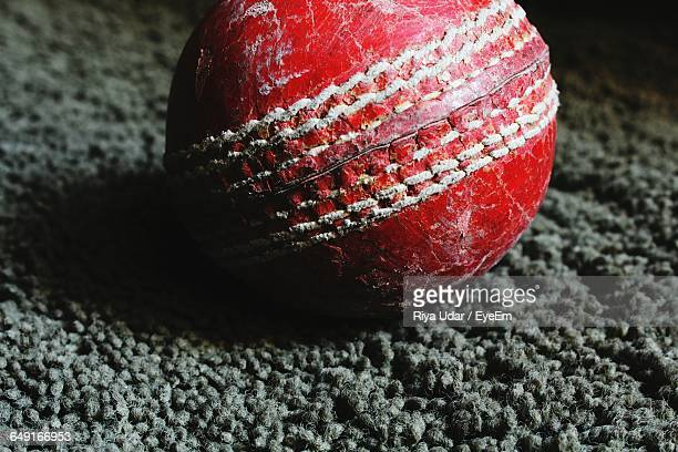 Close-Up Of Red Cricket Ball On Rug At Home