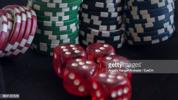 close-up of red dice and gambling chips on black table - gambling table stock pictures, royalty-free photos & images