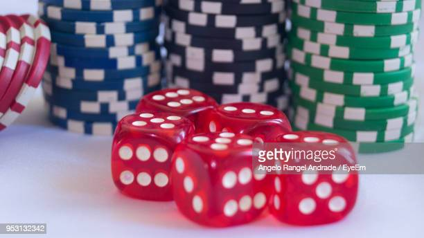 close-up of red dice and gambling chips on white table - gambling table stock pictures, royalty-free photos & images