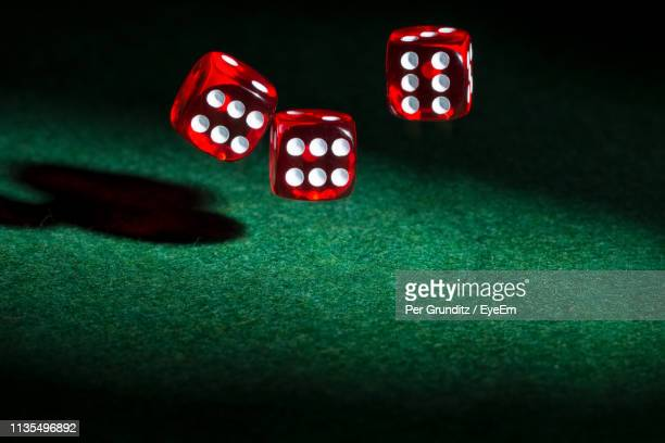 close-up of red dices in mid-air over green table - three objects stock pictures, royalty-free photos & images