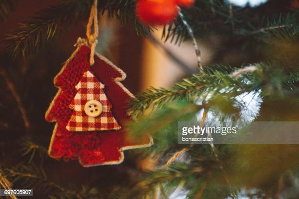 close-up of red fabric decor on christmas tree - bortes stockfoto's en -beelden