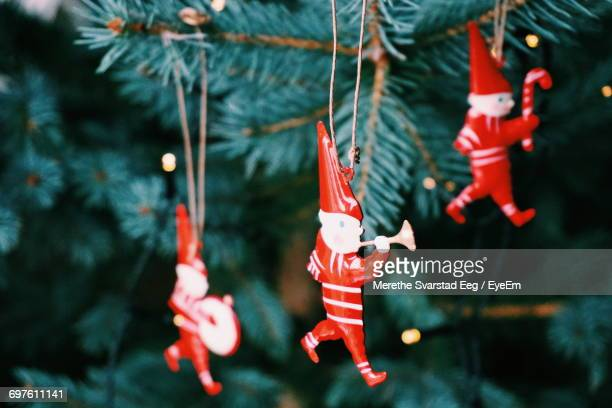 Close-Up Of Red Figurines Hanging On Christmas Tree