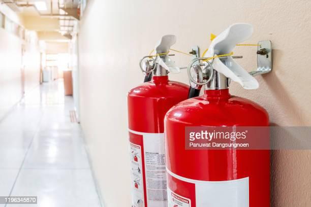 close-up of red fire extinguisher at corridor - 消火器 ストックフォトと画像