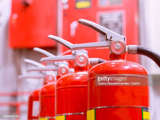 close-up of red fire extinguishers - fire extinguisher stock photos and pictures