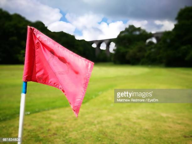 close-up of red flag on golf course against sky - golf flag stock photos and pictures