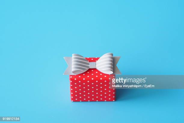 Close-Up Of Red Gift Box Against Blue Background