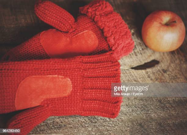 Close-Up Of Red Gloves And Apple On Table
