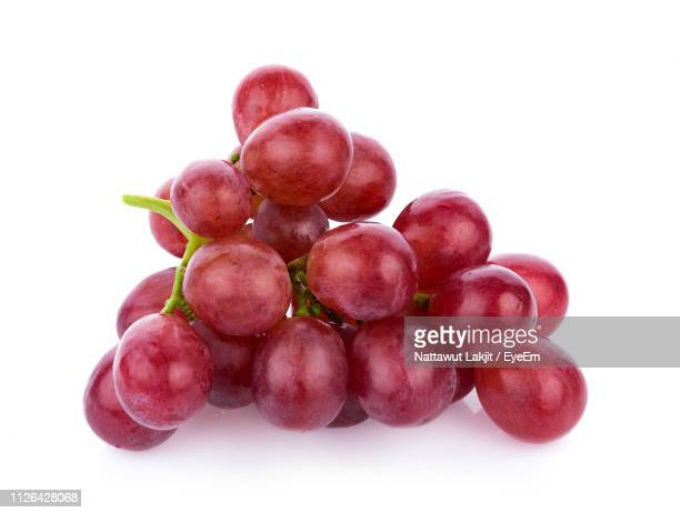 close-up of red grapes against white background - druif stockfoto's en -beelden