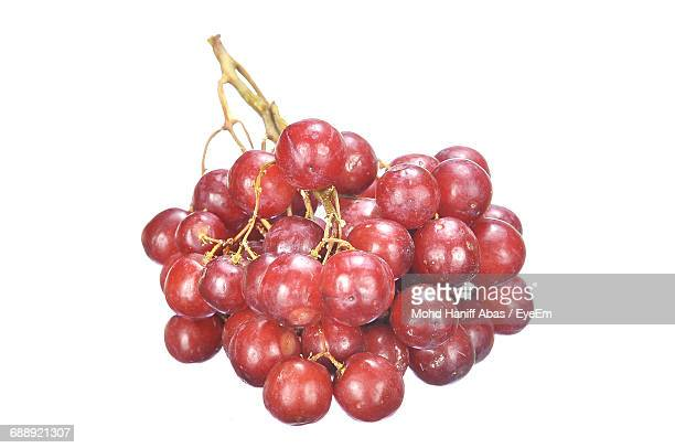 close-up of red grapes on white background - red grape stock photos and pictures