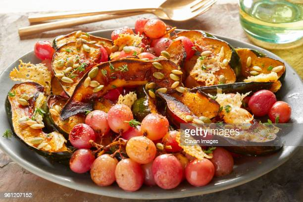 Close-up of red grapes with acorn squash in plate on table