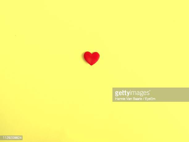 Close-Up Of Red Heart Shape Against Yellow Background