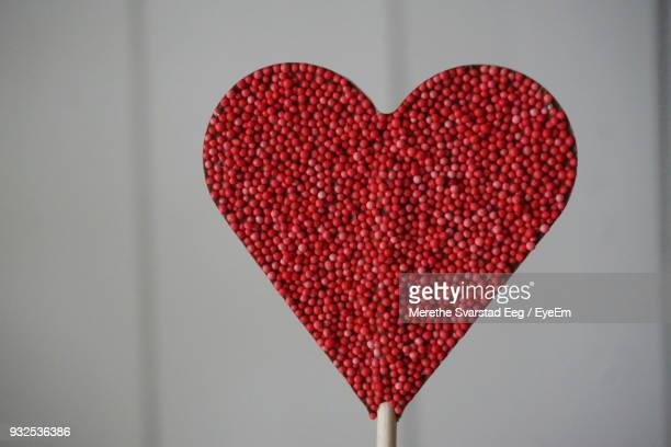 Close-Up Of Red Heart Shape Candy Against Wall