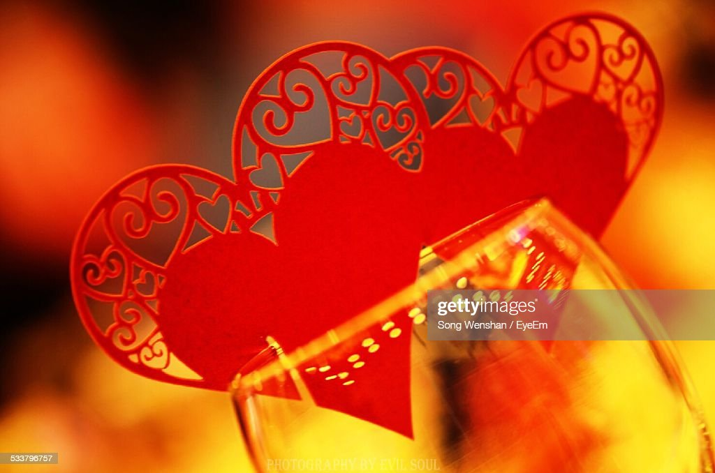 Close-Up Of Red Heart Shape Decorations Attached On Drinking Glass : Foto stock
