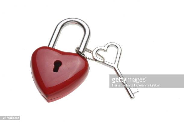 close-up of red heart shaped lock with key on white background - padlock stock photos and pictures