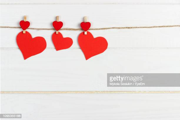 close-up of red heart shapes on string at table - clothespin stock pictures, royalty-free photos & images