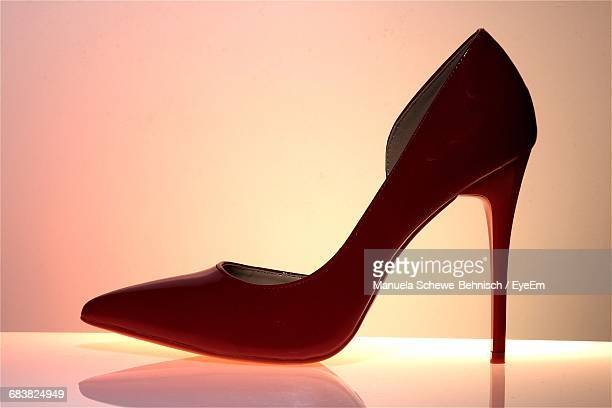 Close-Up Of Red High Heels On Table Against White Background