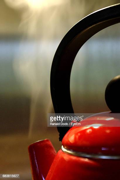 close-up of red kettle in kitchen at home - red kettle stock photos and pictures