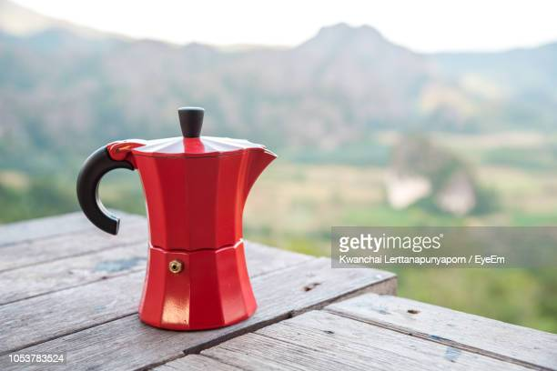 close-up of red kettle on wooden table against mountain - red kettle stock photos and pictures