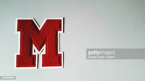 Close-Up Of Red Letter M On White Background
