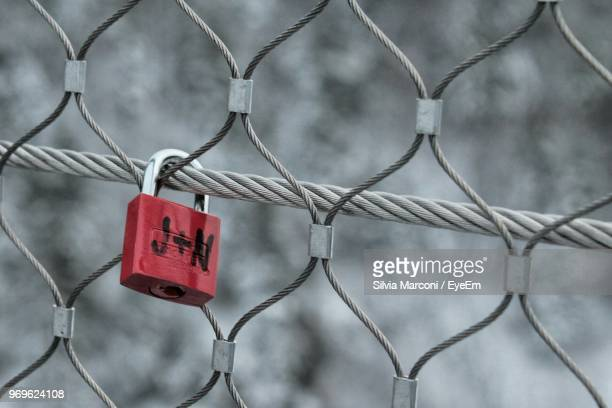close-up of red padlock on chainlink fence - letter n stock pictures, royalty-free photos & images