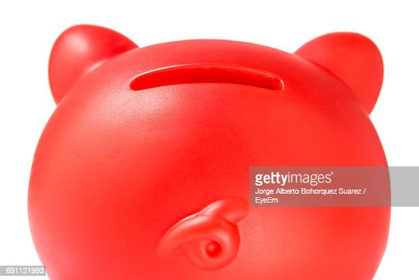 Close-Up Of Red Piggy Bank Against White Background
