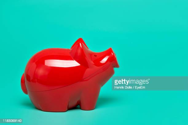close-up of red piggy bank on green background - objet rouge photos et images de collection