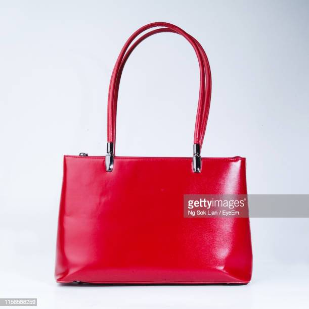 close-up of red purse against white background - leather purse stock pictures, royalty-free photos & images