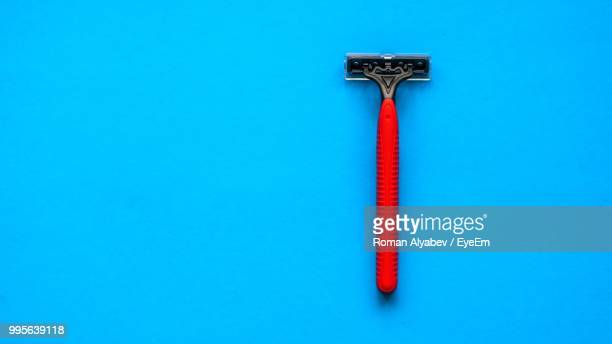 close-up of red razor over blue background - razor stock photos and pictures