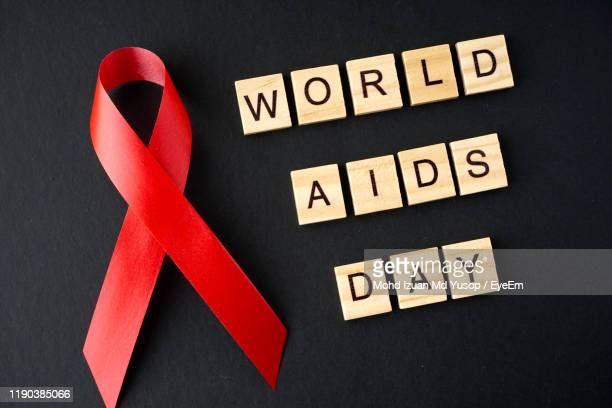close-up of red ribbon by world aids day text over black background - world aids day stock pictures, royalty-free photos & images