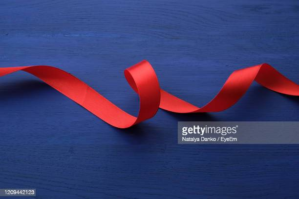 close-up of red ribbon on table - curled up stock pictures, royalty-free photos & images