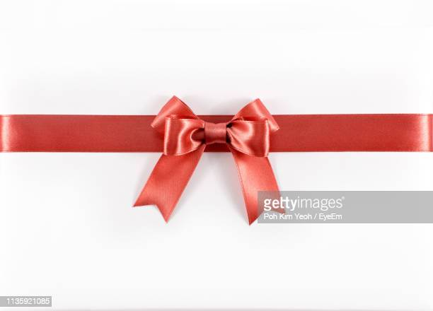 close-up of red ribbon on white background - ribbon stock pictures, royalty-free photos & images
