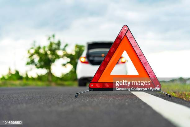 close-up of red road sign on road against sky - vehicle breakdown stock pictures, royalty-free photos & images