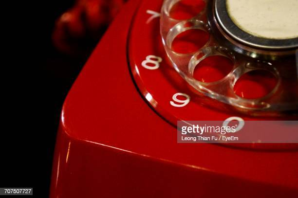 Close-Up Of Red Rotary Phone Against Black Background