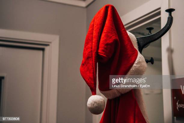close-up of red santa hat hanging from rack at home - santa hat stock pictures, royalty-free photos & images