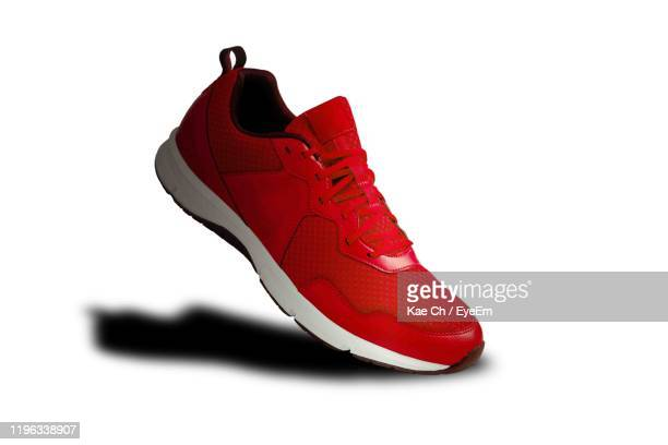 close-up of red shoe over white background - red shoe stock pictures, royalty-free photos & images