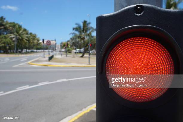 close-up of red stoplight by road in city - red light stock pictures, royalty-free photos & images